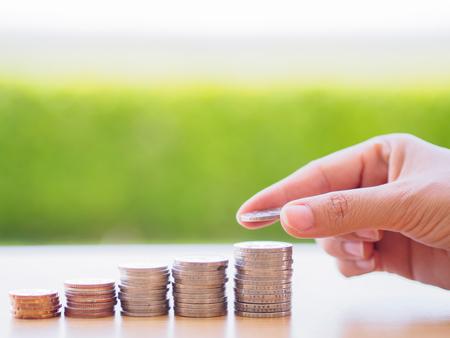 abstrakte Geld sparen Hand eine Münze auf Stapeln Münzen Standard-Bild