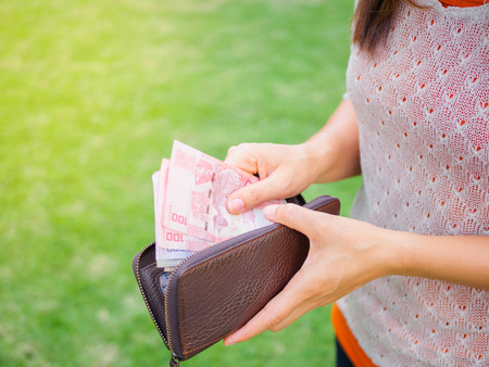Women Hands taking out money thai baht from wallet on the green grass field Stock Photo