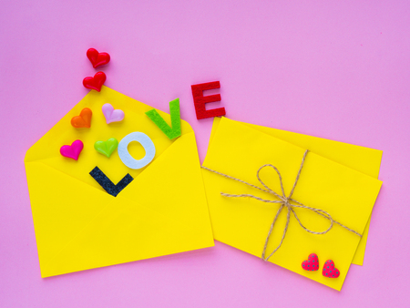 love letter concept. Opened envelope and many felt hearts. colorful of hearts with LOVE text on pink background. Stock Photo