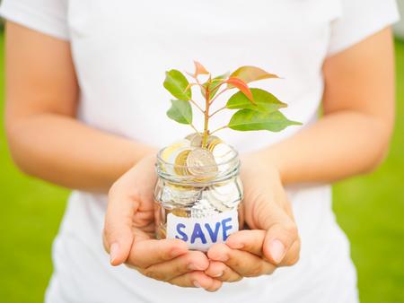 Las mujeres dan la planta que crece fuera de monedas en el tarro de cristal en la hierba verde para el concepto financiero del ahorro del dinero Foto de archivo