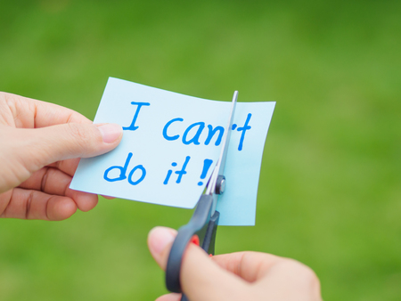 Women using scissors to remove the word can't to read I can do it concept for self belief, positive attitude and motivation
