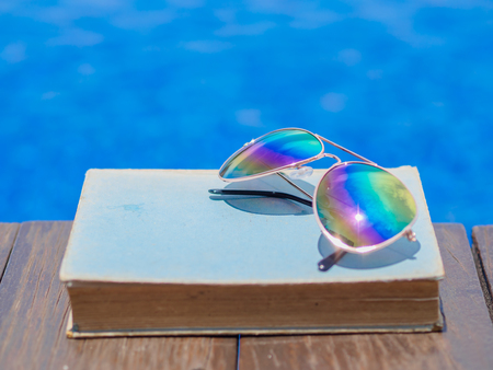 Book and sunglasses, blue water background, summer and tropical travel destinations concept Stock Photo