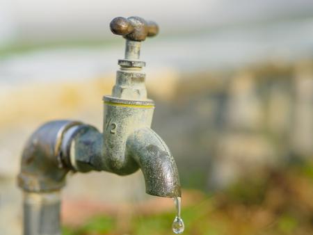 近くには古いとグランジ蛇口、水滴、水不足概念。
