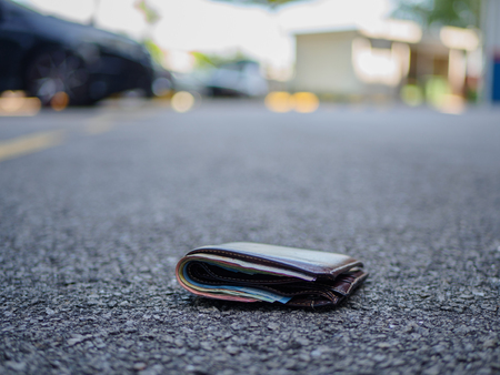 wallet with money drop on the street, lost money concept, copy space on top