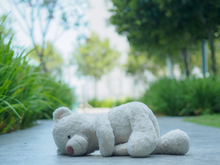 Lonely Teddy Bear sleeping on the walk way or road (Concept about love) Stock Photo