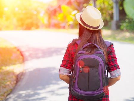 道路や森林の背景、概念の休日旅行、ビンテージ トーンとソフト フォーカスの色にくつろぐのための時間に満足しているアジア女の子バックパック