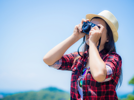 Outdoor summer lifestyle portrait of pretty young woman having fun in the jungle. Photographer making pictures in hipster style glasses and hat. Stock Photo