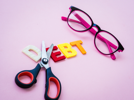 arrears: cut dept concept with text, pink glasses and scissor