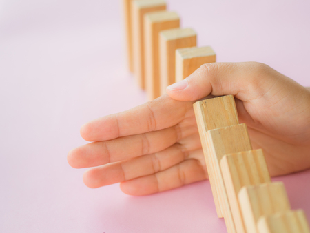 Solution concept with hand stopping wooden blocks from falling in the line of domino Stock Photo