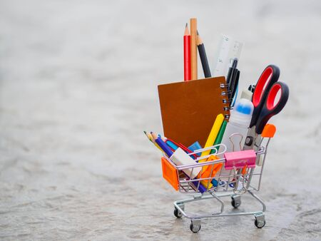 Shopping cart with school supply. Back to school concept.