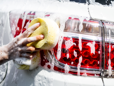 Woman hand with yellow sponge washing car