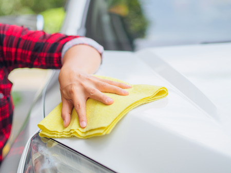 valeting: Hand with yellow microfiber cloth cleaning white car. Stock Photo