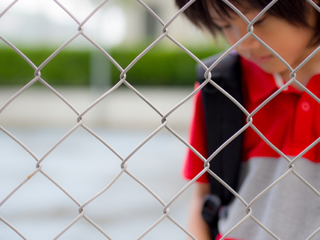 Portrait of handsome sad boy behind fence mesh netting. Emotions concept - sadness, sorrow, melancholy. Fashion & beauty concept. Stock Photo