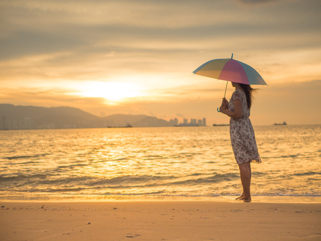 Lonely and depressed woman holding an umbrella and standing in front of the sea in a deserted beach on an Autumn day.