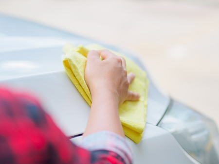 Hand with yellow microfiber cloth cleaning white car. Stock Photo