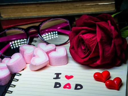 Fathers day concept. I LOVE DAD message write on note book with red rose, stack of books, glasses and  sweet marshmallow in the shape of heart on dark background