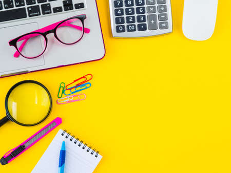 Flat lay, top view office table desk frame. feminine desk workspace with office accessories including calculator, mouse laptop, glasses, clips, Magnifying glass, cutter, note book and blue pen on yellow background.
