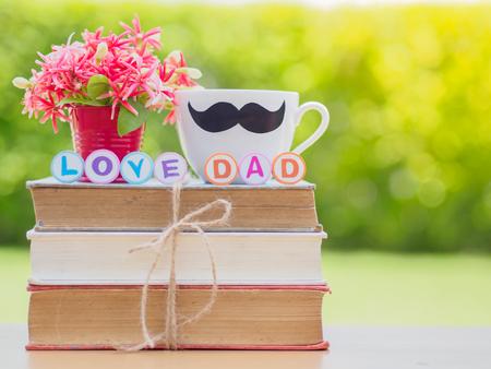 父亲节的概念。爱爸爸字母在一堆书,礼物,茶杯与黑胡子和花的背景
