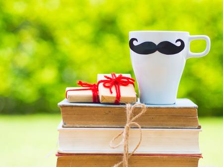 父亲节的概念。书籍、礼品、黑胡子茶杯、花朵背景的黑白堆叠
