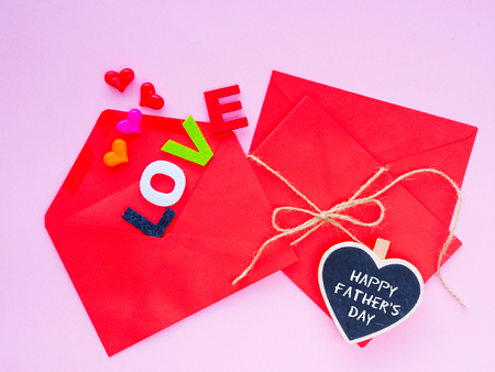 Happy Fathers day love letter concept. Opened envelope and many felt hearts. colorful of hearts with LOVE text on pink background.