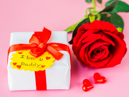 Fathers day concept. I LOVE YOU DADY message with red rose, two red heart and gift on pink background