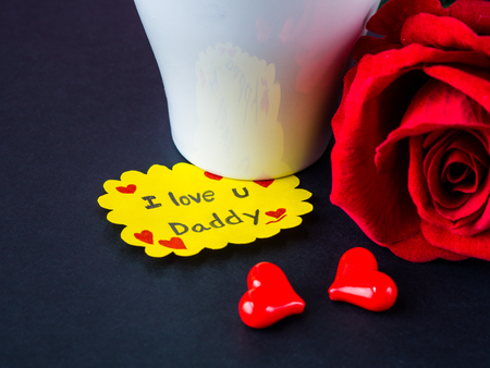 Fathers day concept. I LOVE YOU DADY message with red rose, two red heart and gift on black background Stock Photo