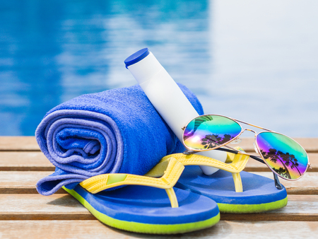 flip flops, sunglasses, blue towel and sunscreen at the side of swimming pool. Vacation, beach, summer travel concept