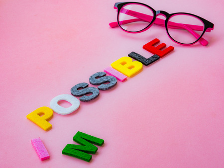 overcoming adversity: cut the word impossible to possible. Alphabet I, M being cut. Change concept. Stock Photo