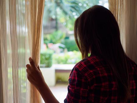 Tylni widok młoda kobieta trzyma zasłony otwiera patrzeć z wielkiego lekkiego okno w domu, wnętrze. Pozytywny i aspiracyjny styl życia. Smutna kobieta przyglądająca out okno, indoors.