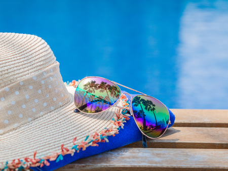 Beach hat, sunglasses, blue towel and sunscreen at the side of swimming pool. Vacation, beach, summer travel concept