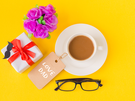 Fathers day concept. Happy Fathers Day and I LOVE DAD message on note book with pink flower, coffee cup, white gift and black Mustache on yellow background Stock Photo