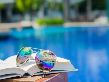 スイミング プールの側の開いた本のサングラス。休暇、ビーチ、夏旅行の概念 写真素材