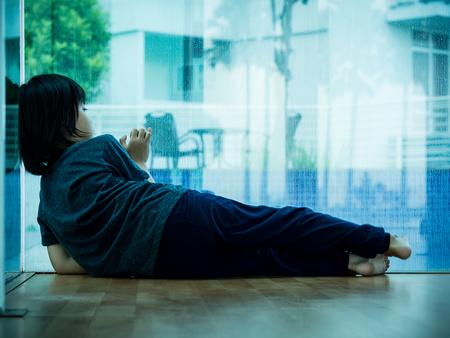 stitting: little boy unhappy sad stitting in empty room and tress alone. Sad child concept.