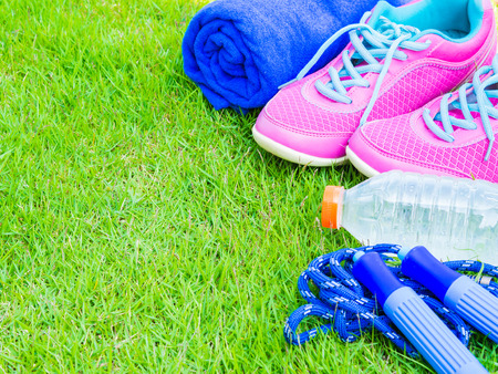 earbud: Pair of pink sport shoes, towel, earphone, water bottle and Jump rope on green grass field. In the background forest or park trail. Accessories for running sport. Stock Photo