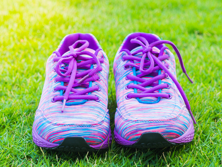 earbud: Pair of pink sport shoes and water bottle on green grass field. In the background forest or park trail. Accessories for running sport. Stock Photo