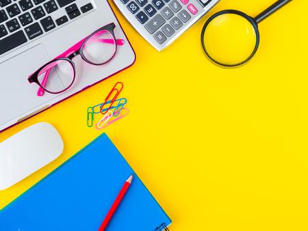 Plat leggen, bovenaanzicht kantoor tafel bureau frame. vrouwelijke bureau werkruimte met kantooraccessoires, waaronder rekenmachine, muis laptop, bril, clips, vergrootglas, schaar, notitieboek en blauwe pen op gele achtergrond.