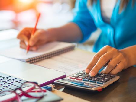 vrouw werken met rekenmachine, zakelijk document en laptop notebook