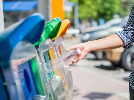 Closeup portrait woman hand throwing empty plastic water bottle in recycling bin.