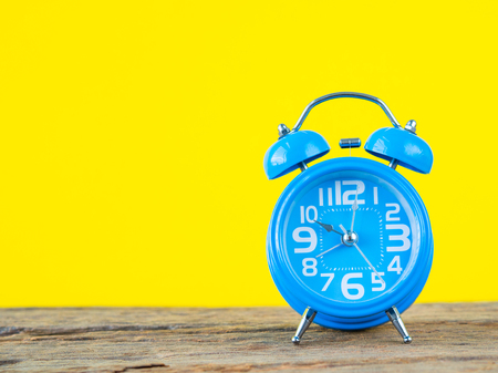 Close up Alarm clock on wooden and yellow background. Time concept.