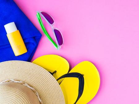 Zonnebril met zomer hoed, flip flops, blauwe handdoek en zonnebrand lotion op roze achtergrond. Vakantie en ontspanning, zomer reizen concept.