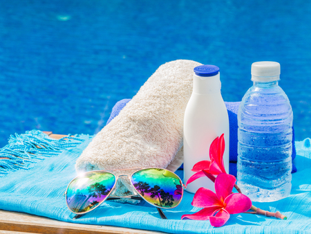 Red frangipani (plumeria) flowers, sunglasses, sunscreen, blue and white towels at the side of swimming pool. Vacation, beach, summer travel concept