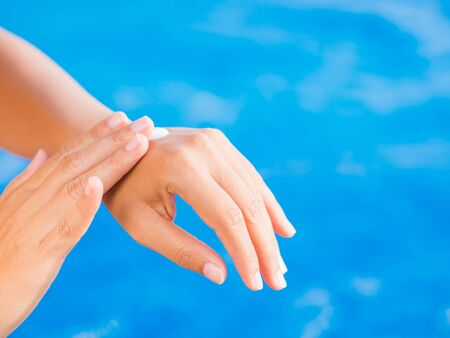 Woman hand apply sunscreen  sunblock by the swimming pool. Vacation and relaxation, summer travel concept.
