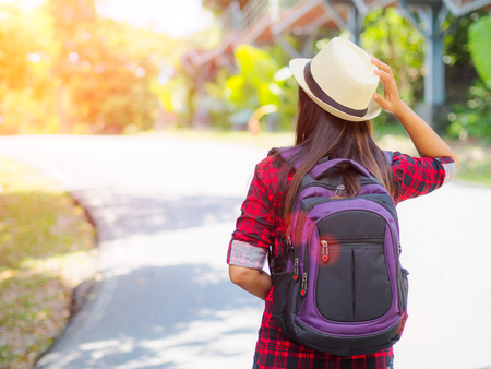 Happy Asian girl backpack in the road and forest background, Relax time on holiday concept travel. Stock Photo