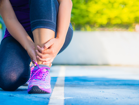 Young woman suffering from an ankle injury while exercising and running. Sport  excercise concept. Stockfoto
