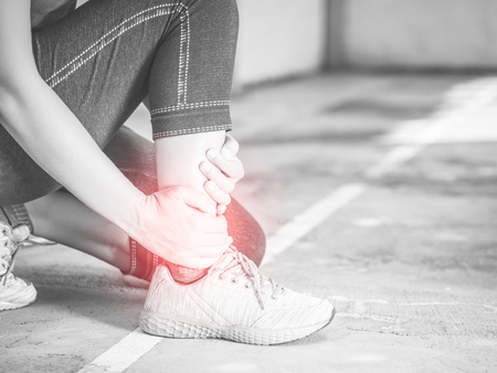 Black and white young woman suffering from an ankle injury while exercising and running. Sport  excercise concept. Stock Photo