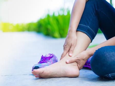 Mujer joven que sufre de una lesión de tobillo durante el ejercicio y el funcionamiento. Concepto de ejercicio deportivo. Foto de archivo