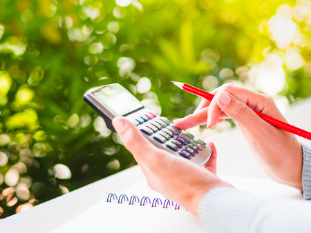 woman hand working with calculator and holding red pencil, business document and note book on working table with nature green leaves background.