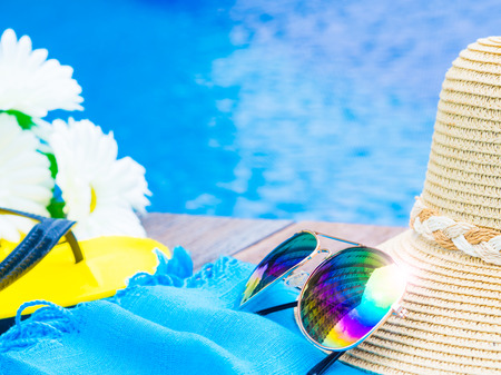 Sunglasses with summer hat, flip flops   and flowers by the swimming pool. Vacation and relaxation, summer travel concept.