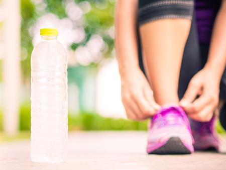 ランニング シューズ - 水のボトルと靴ひもを結ぶ女性のクローズ アップ。女性スポーツ フィットネス ランナー庭 backgroound でジョギングの準備
