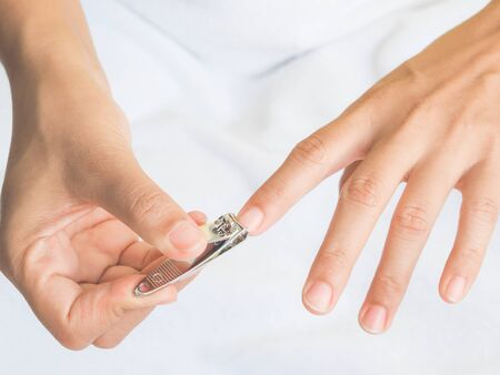 Closeup of a woman cutting nails, health care concept.